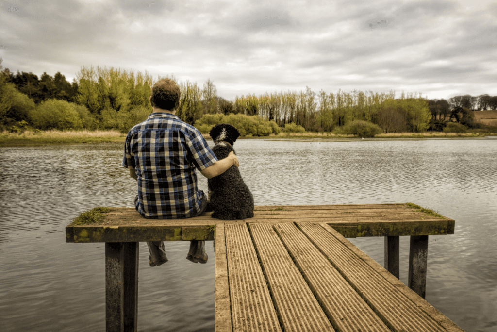 a man sitting next to a brown dog on a dock
